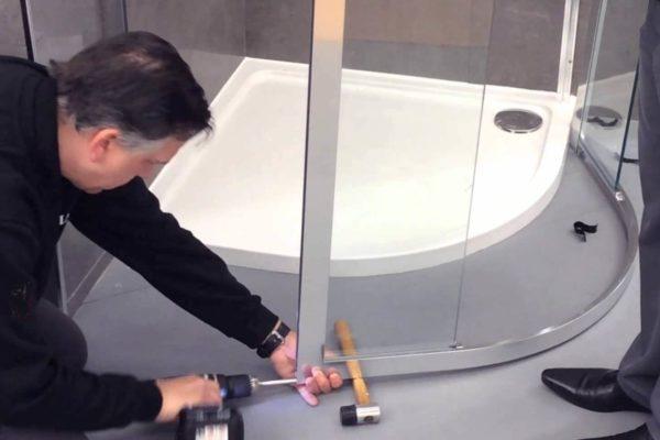 Мастер устанавливает душевую кабину в ванной